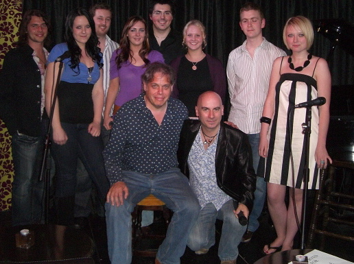 Photo: David Stark and host Tony Moore with performers Katherine Elizabeth, Sam Sanderson, Kate Threlfall, Andy Coleman and Kate Clague, along with their backing musicians.